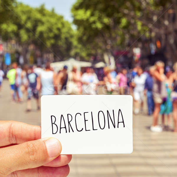 Stock photo: man at Las Ramblas shows a signboard with the word Barcelona