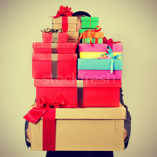 young man in suit carrying a pile of gift boxes, with a filter e Stock photo © nito
