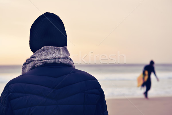 man wearing coat, scarf and knit cap in front of the ocean Stock photo © nito