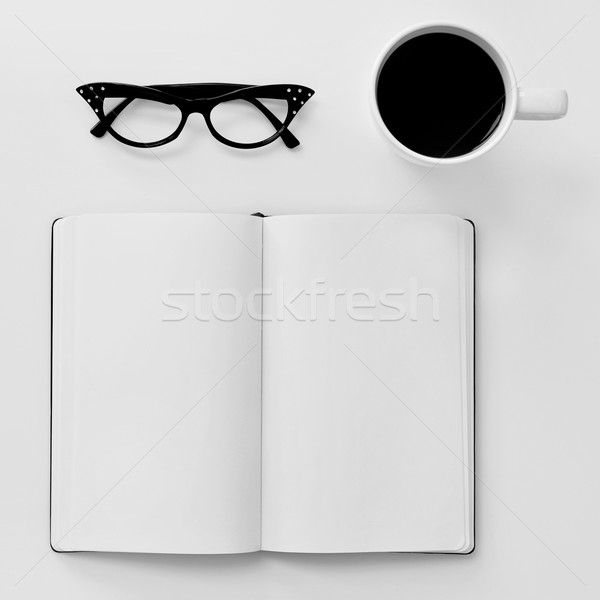 blank notebook, eyeglasses and cup of coffee on a white table Stock photo © nito