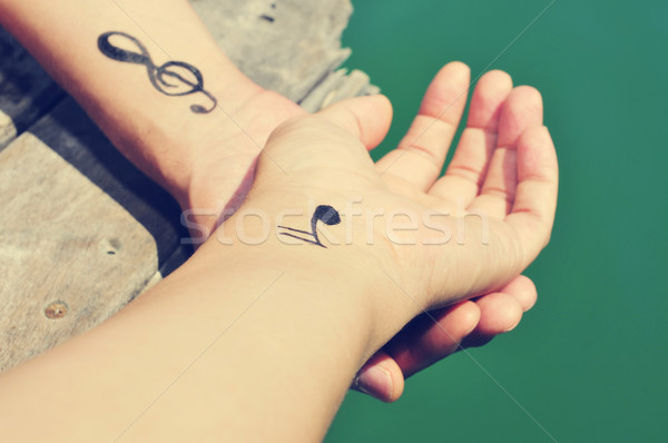 a young man with some musical symbols tattooed in his wrists Stock photo © nito