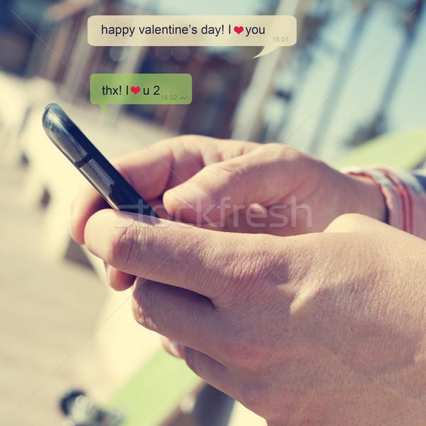 Boldog valentin nap szöveges üzenet fiatalember küldés okostelefon Stock fotó © nito