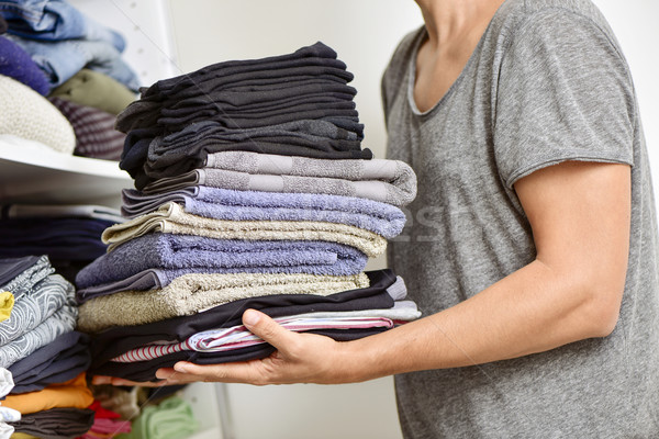 young man with a pile of folded clothes Stock photo © nito