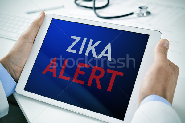 doctor with a tablet with the text zika alert Stock photo © nito