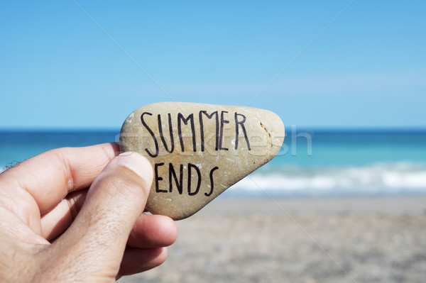 Stock photo: man on the beach and text summer ends in a stone