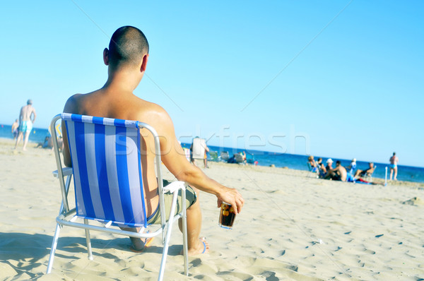 young man hanging out on the beach, with a glass with cola drink Stock photo © nito