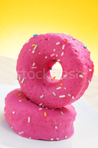 donuts coated with a pink frosting and sprinkles of different co Stock photo © nito