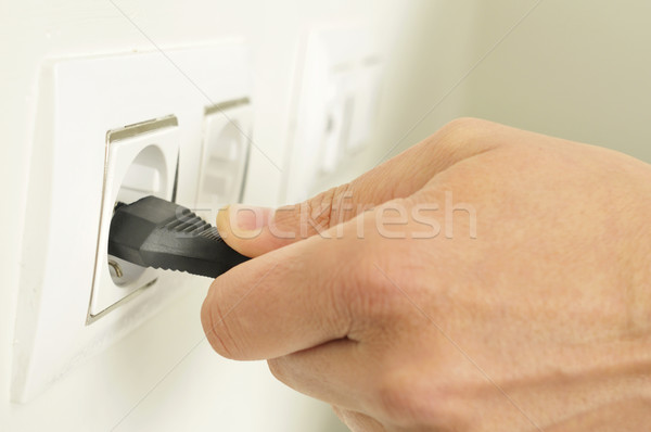man plugging in or unplugging an electrical plug in a socket Stock photo © nito
