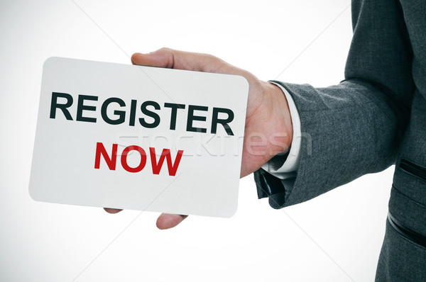 Stock photo: man shows a signboard with the text register now