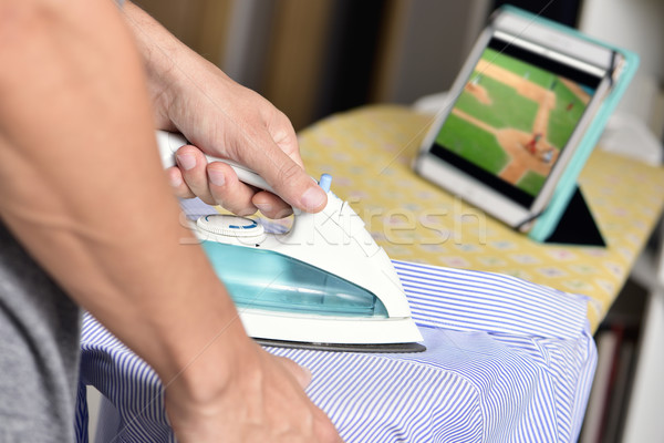 young man ironing a shirt while watching sports online Stock photo © nito