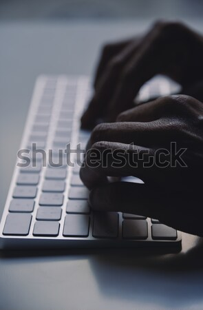 young man typing in a computer keyboard Stock photo © nito