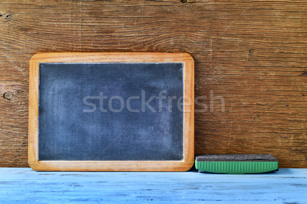 blank chalkboard and an eraser on a blue wooden table Stock photo © nito