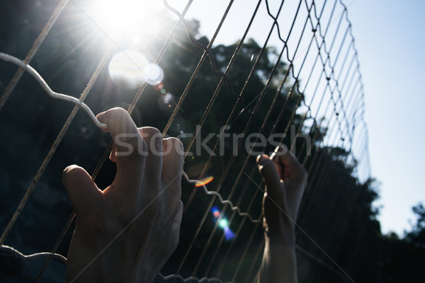 man climbing up a metal fence Stock photo © nito