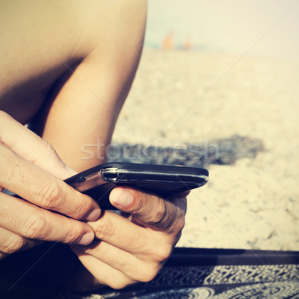 young man using a smartphone on the beach, filtered Stock photo © nito
