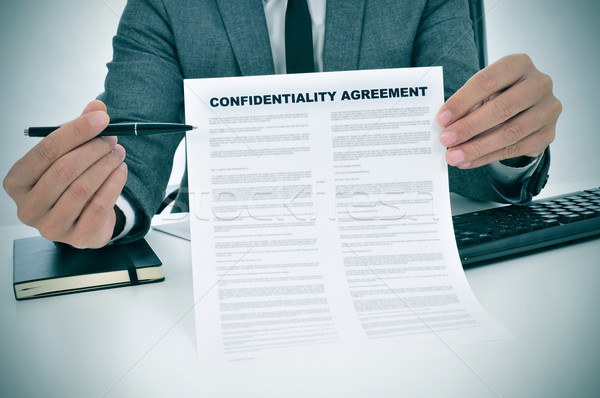 Stock photo: young man showing a confidentiality agreement document