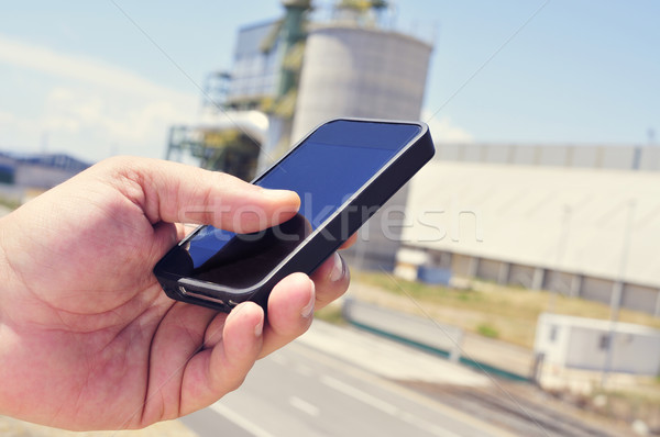 man using a smartphone in an industrial park Stock photo © nito