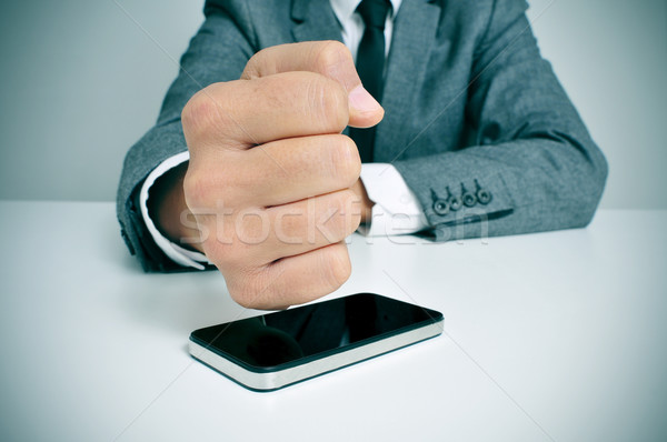 businessman hitting a smartphone with his fist Stock photo © nito