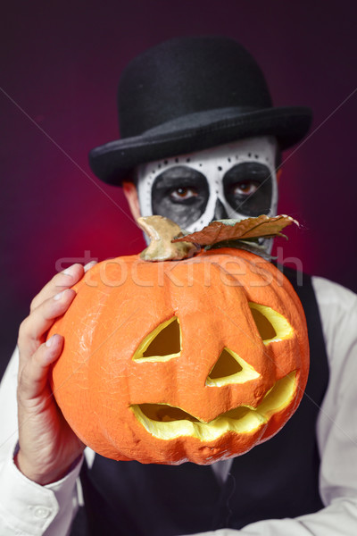 man with mexican calaveras makeup and carved pumpkin Stock photo © nito