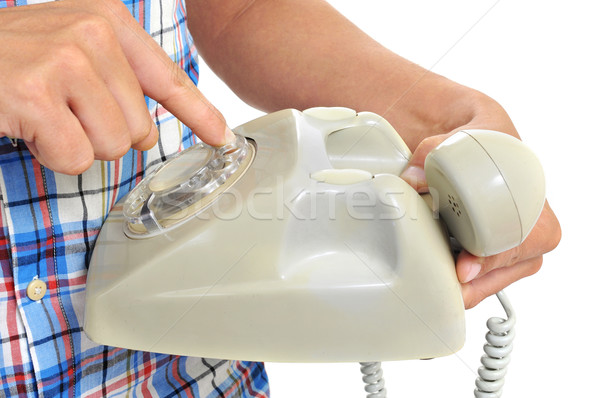 young man dialing in a rotary dial telephone Stock photo © nito