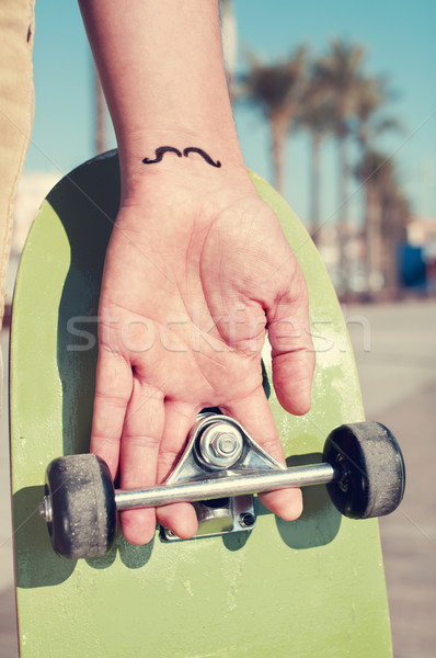 young man with a moustache tattooed in his hand, holding a skate Stock photo © nito
