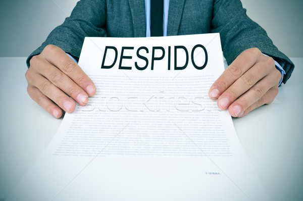 businessman shows a document with the text despido, dissmissal i Stock photo © nito