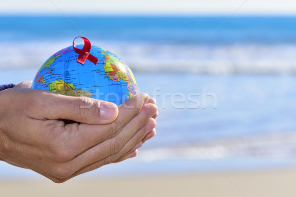 young man with a world globe with a red ribbon Stock photo © nito