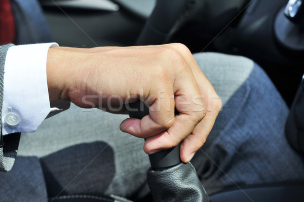 Stock photo: man in suit operating the parking brake of a car