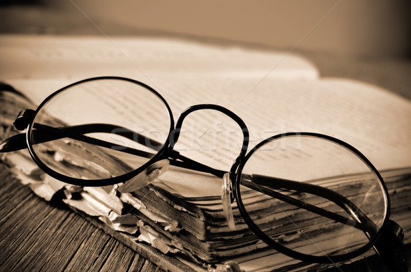 round-framed eyeglasses and old book, in sepia toning Stock photo © nito