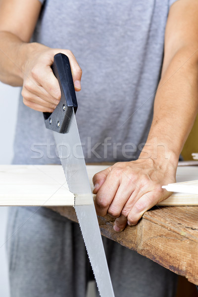 young man sawing a wooden board with a handsaw Stock photo © nito