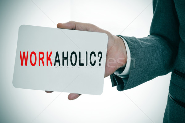 businessman showing a signboard with the word workaholic Stock photo © nito