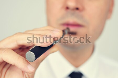 young man vaping with an electronic cigarette Stock photo © nito