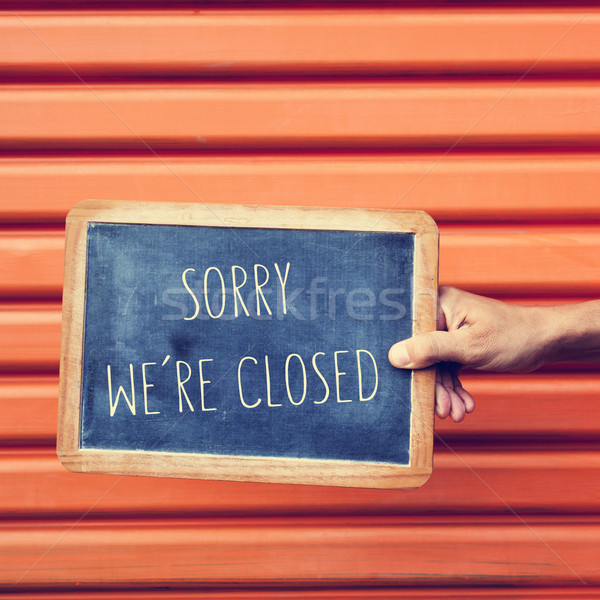 man hand with a chalkboard with the text sorry we are closed Stock photo © nito
