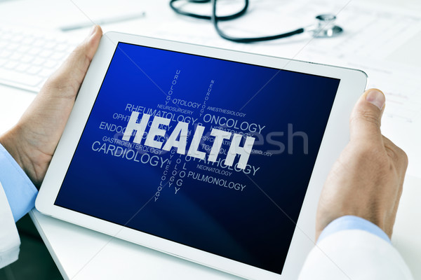doctor with a tablet with a tag cloud about health Stock photo © nito
