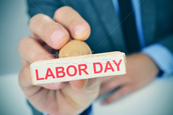young man with a rubber stamp with the text labor day Stock photo © nito