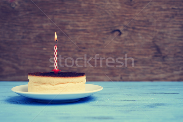 Stock photo: lighted birthday candle on a cheesecake, with a retro effect