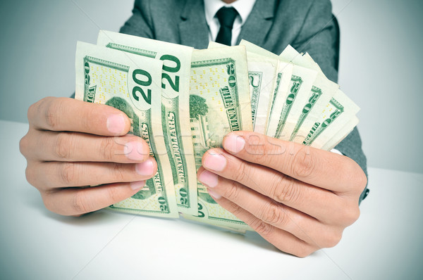 man in suit counting US dollar bills Stock photo © nito