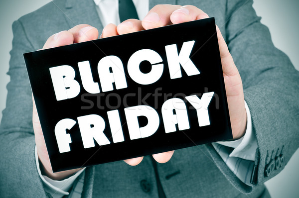 man in suit with a signboard with the text black friday Stock photo © nito