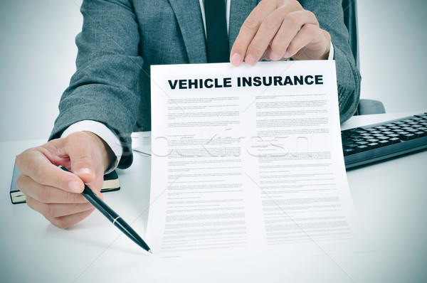 young man in suit showing a vehicle insurance policy Stock photo © nito