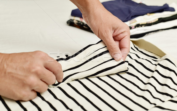 young man folding clothes Stock photo © nito