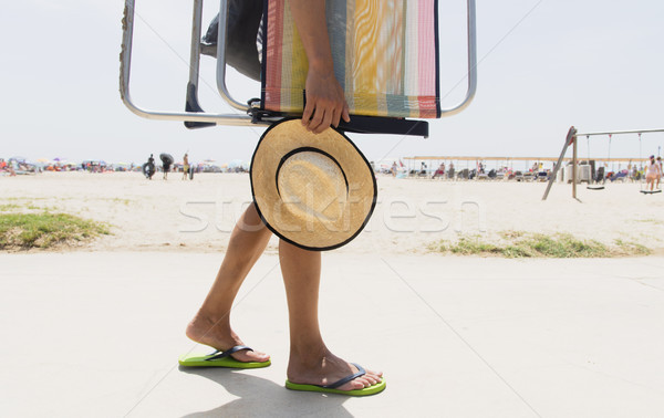 Stock photo: young man carrying a beach chair