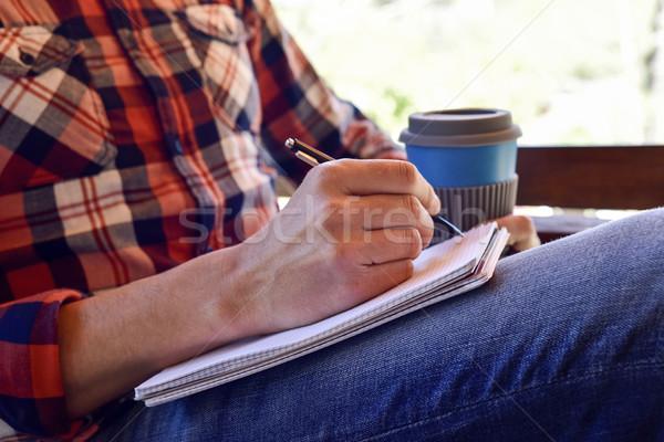 Młody człowiek piśmie notebooka młodych Zdjęcia stock © nito