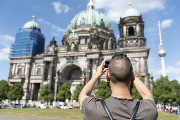 Stock photo: young man taking a picture of the Berlin Cathedral