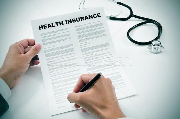 Młody człowiek podpisania ubezpieczenie zdrowotne polityka biuro Zdjęcia stock © nito