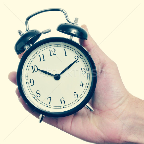 man hand holding a mechanical alarm clock, with a retro effect Stock photo © nito