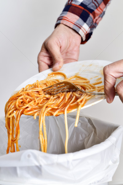 young man throwing leftovers to the trash bin Stock photo © nito