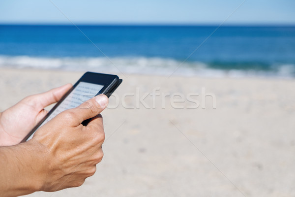 man reading in a tablet or e-reader on the beach Stock photo © nito