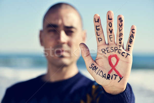 young man with a red ribbon for the fight against AIDS in his ha Stock photo © nito