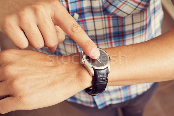 young man tapping his finger on his wristwatch  Stock photo © nito