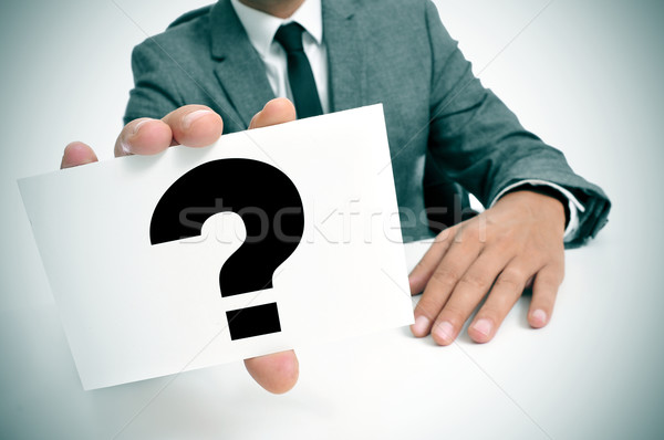 man in suit holding a signboard with a question mark Stock photo © nito