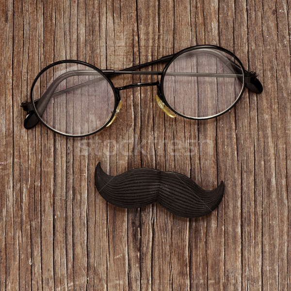 eyeglasses and mustache on a wooden surface Stock photo © nito